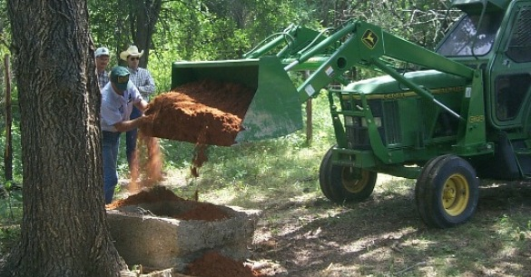 Filing an abandoned well with a clay mixture per plugging procedures.