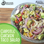 chipotle chicken taco salad recipe plated and ready for eating in a silver beaded bowl, resting on a wooden cutting board